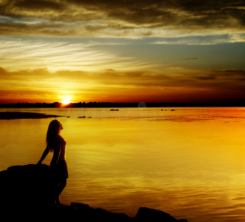 Beautiful girl on sundown. Silhouette the woman of the river, worth on a coast royalty free stock images