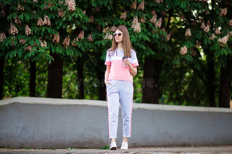 Beautiful girl in sunglasses walk by summer street with coffee. stock photos