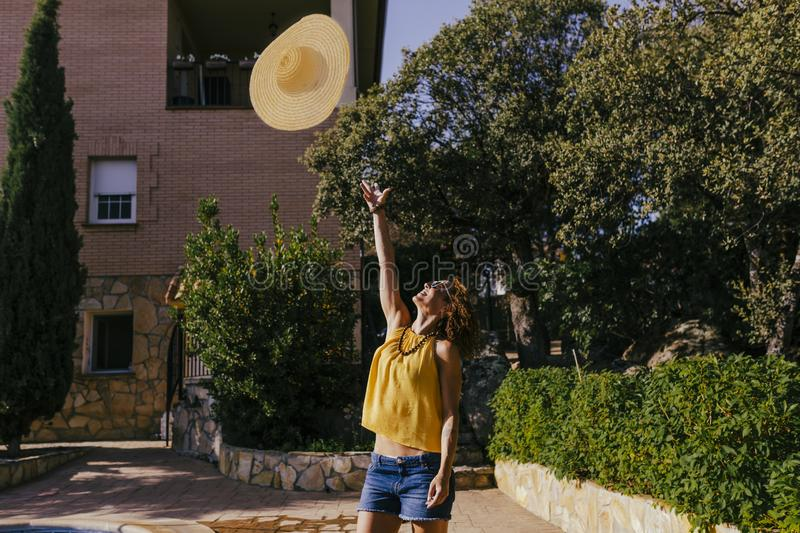 Beautiful girl at sunset holding a hat in her hand and throwing it into the air. Summer, fun and lifestyle outdoors. Freedom, person, smiling, young, modern royalty free stock photography