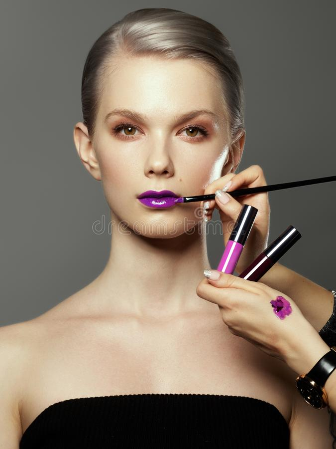 Beautiful girl surrounded by hands of makeup artists with brushes and lipstick near her face. Photo of happy woman on stock photography