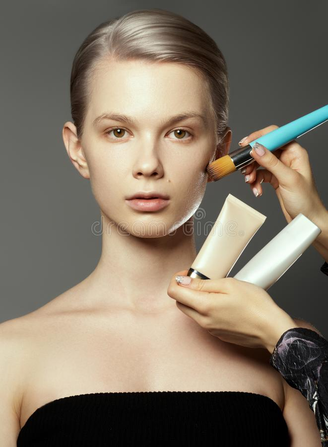 Beautiful girl surrounded by hands of makeup artists with brushes and lipstick near her face. Photo of happy woman on stock photos