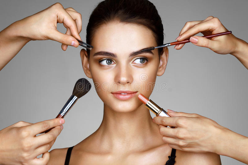 Beautiful girl surrounded by hands of makeup artists with brushes and lipstick near her face royalty free stock photography