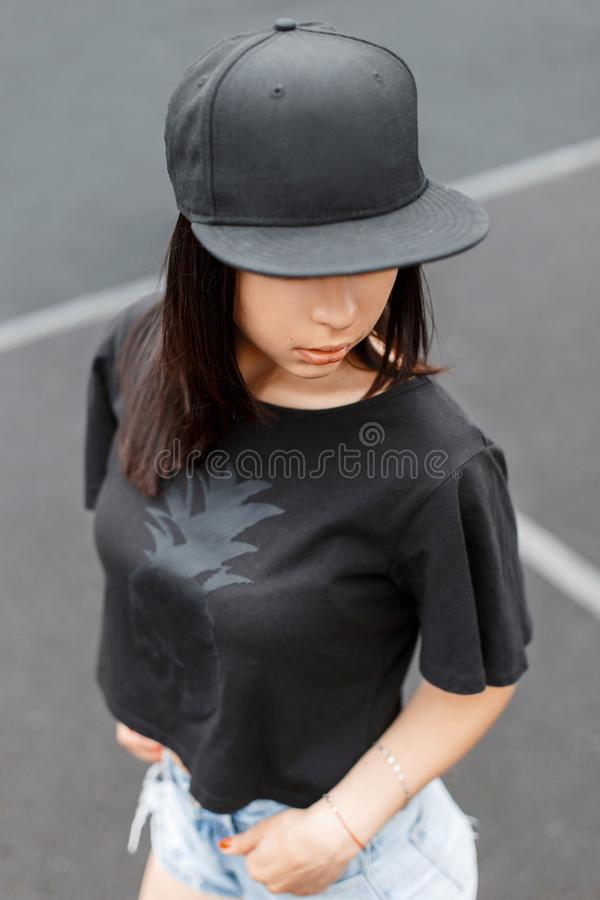 Beautiful girl in swag -style black T-shirt and a cap at the royalty free stock image