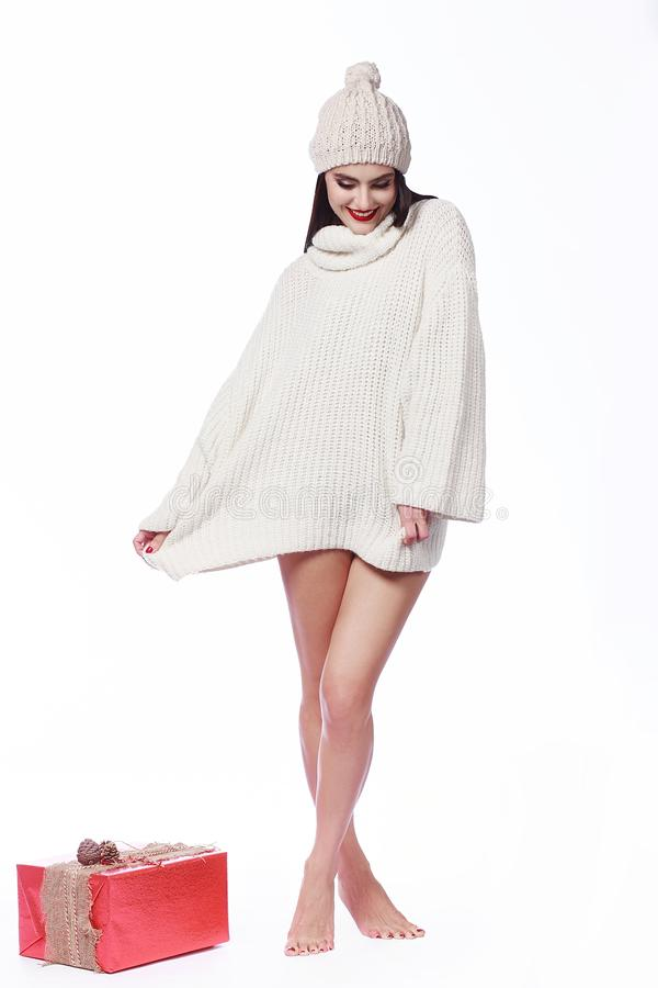 Beautiful girl in a sweater with bare legs in the hat. Beautiful girl in a sweater with bare legs in a knitted hat. In the Studio on a white background stock photos