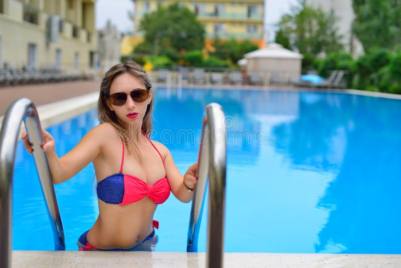 Girl in swimsuit and glasses comes out of the pool royalty free stock images