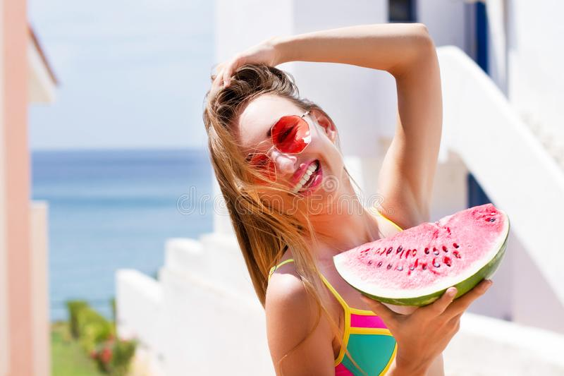 Beautiful girl in a swimsuit and sunglasses holds a piece of watermelon at the resort background hotel. Happy summer woman stock photo