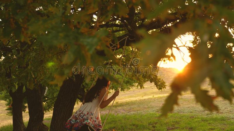 Beautiful girl swinging on a rope swing on an oak branch. young girl in a white dress in the park. teen girl enjoys a. Beautiful girl swinging on a rope swing on stock photo