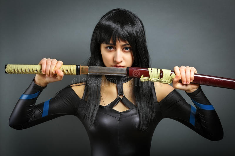 Beautiful girl with sword on grey background. She pulls out the sword royalty free stock photo
