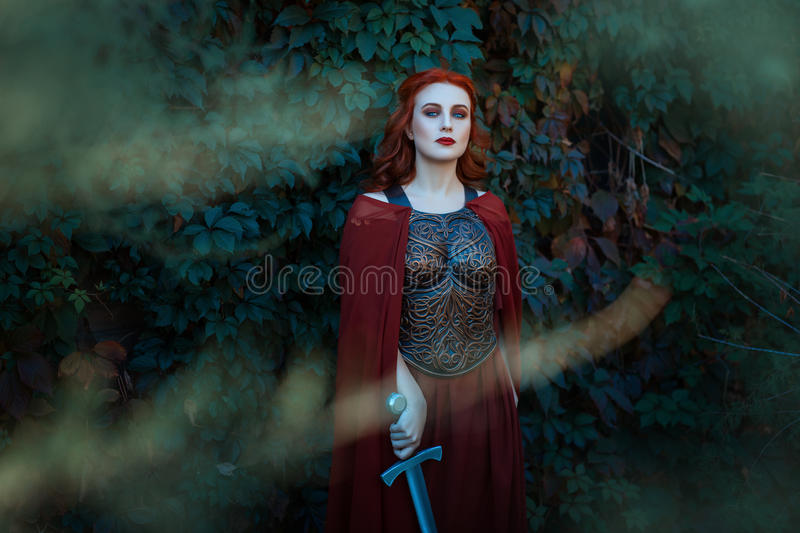 Beautiful girl with a sword standing and looking. royalty free stock photos