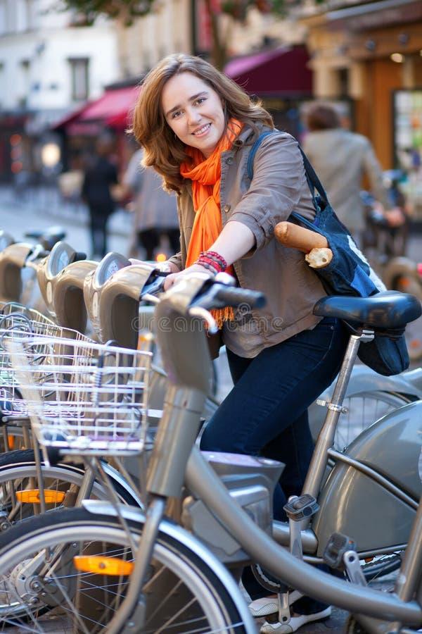 Beautiful girl taking a bike for rent in Paris stock image