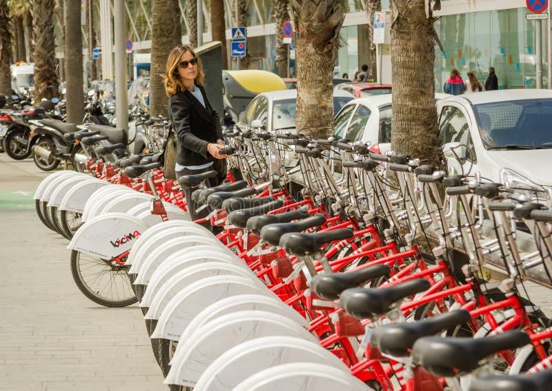 Beautiful girl taking a bike of row on the street, in Barcelona, Spain stock image