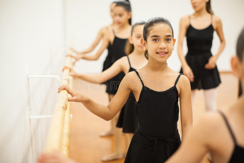 Beautiful girl taking dance lessons at a school. Cute little girl learning how to dance ballet with a group of girls in a dance school stock photography