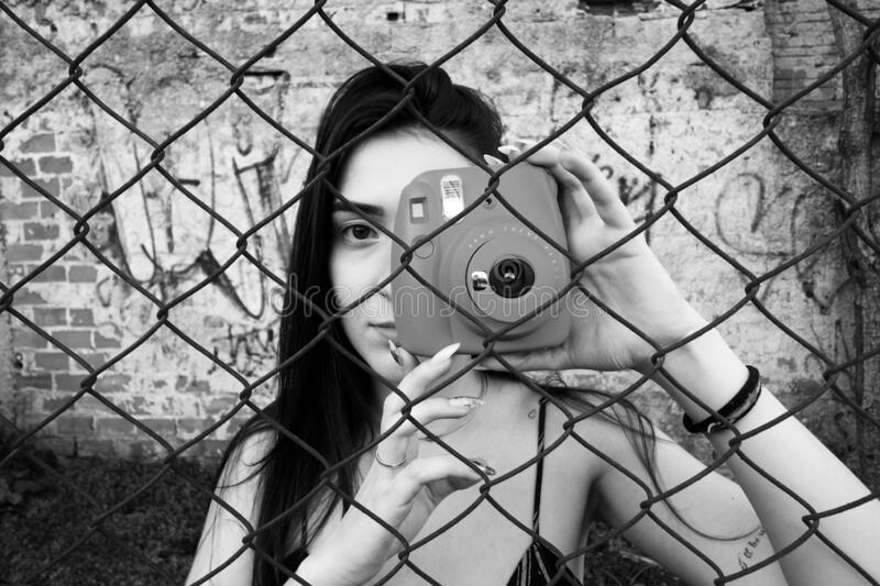 Beautiful girl taking a photo viewed through a fence. Picture of a urban scene, a teenager woman taking a photo in front of a. Graffiti wall. Model facing the stock photo