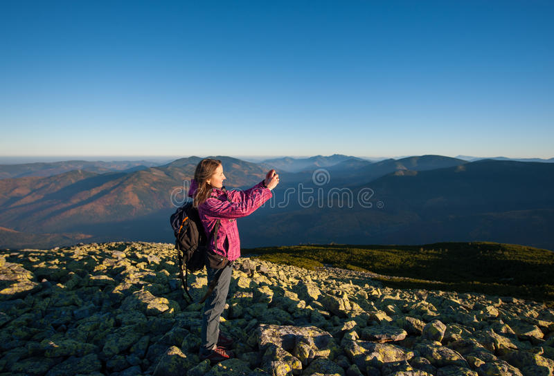 Beautiful girl taking picture with her smartphone in the mountains stock photo