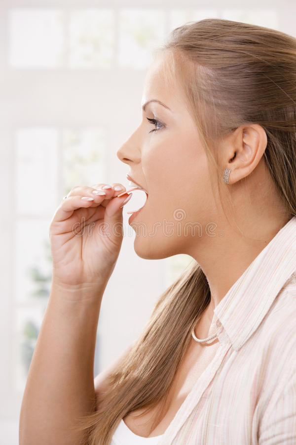 Beautiful girl taking pink chewing gum royalty free stock photography