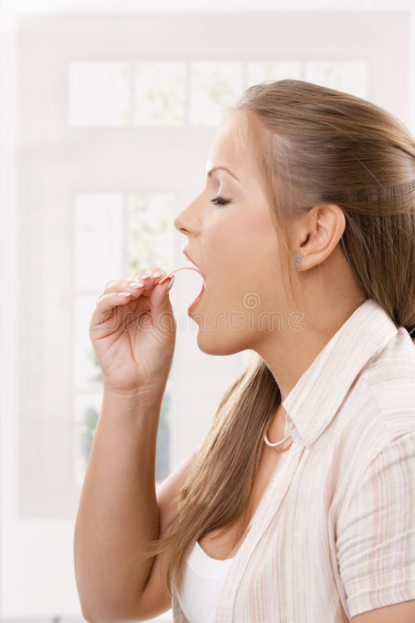 Beautiful girl taking pink chewing gum royalty free stock images