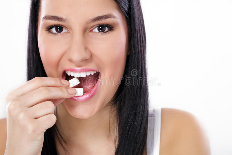 Beautiful girl taking white chewing gum, smiling stock photos