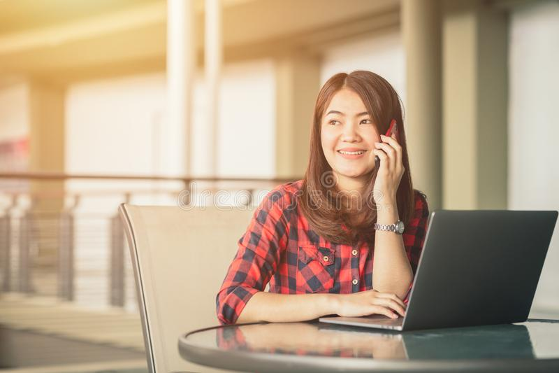 Beautiful girl is talking on the phone happily while sitting and royalty free stock photos