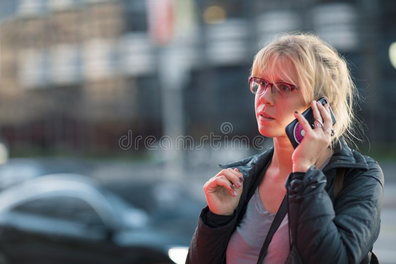 Beautiful girl talking on the phone at night on a busy city street royalty free stock image