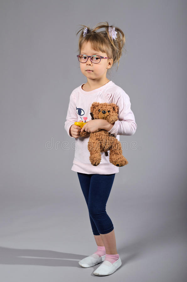 Beautiful girl with a teddy bear on a gray background. stock photography