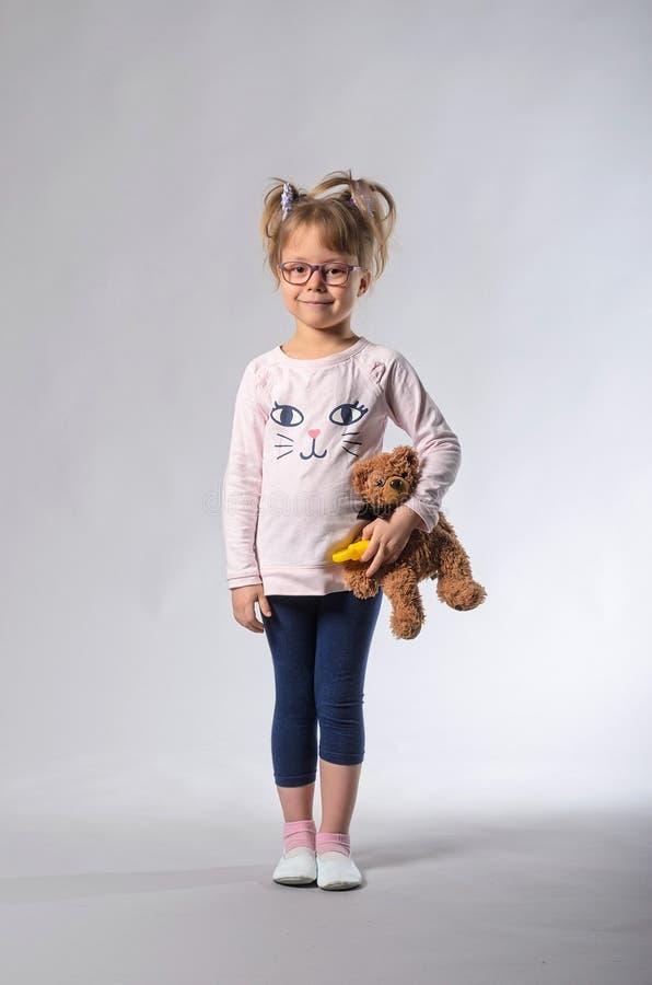 Beautiful girl with a teddy bear on a gray background. stock photos