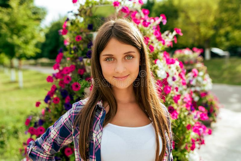 Beautiful girl teenager 13-16 years on the background of a flower bed. Happy smiles. In the summer in city after school royalty free stock photos