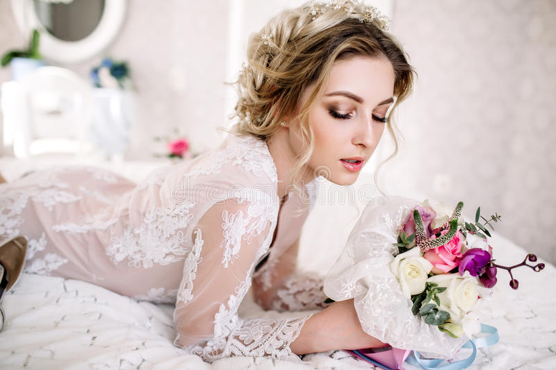Beautiful girl in tender lacy dress with bouquet flowers peonies in hands standing against floral background in flower shop. Joyfu stock image