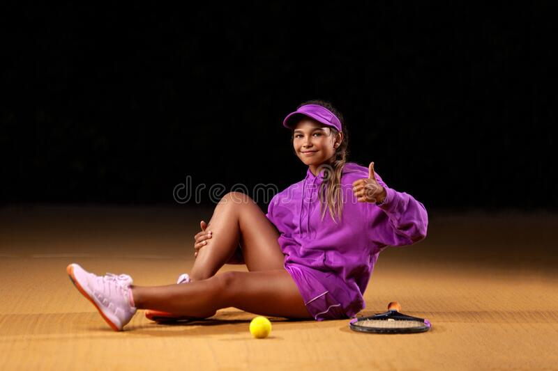 Portrait of kid - tennis player. Beautiful girl athlete with racket in pink sporswear and hat on tennis court. Fashion stock photo