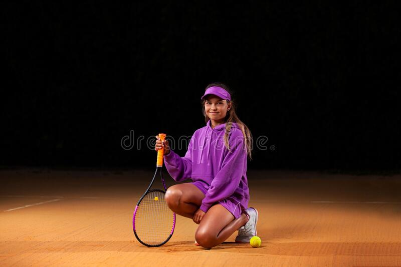 Portrait of kid - tennis player. Beautiful girl athlete with racket in pink sporswear and hat on tennis court. Fashion royalty free stock photos