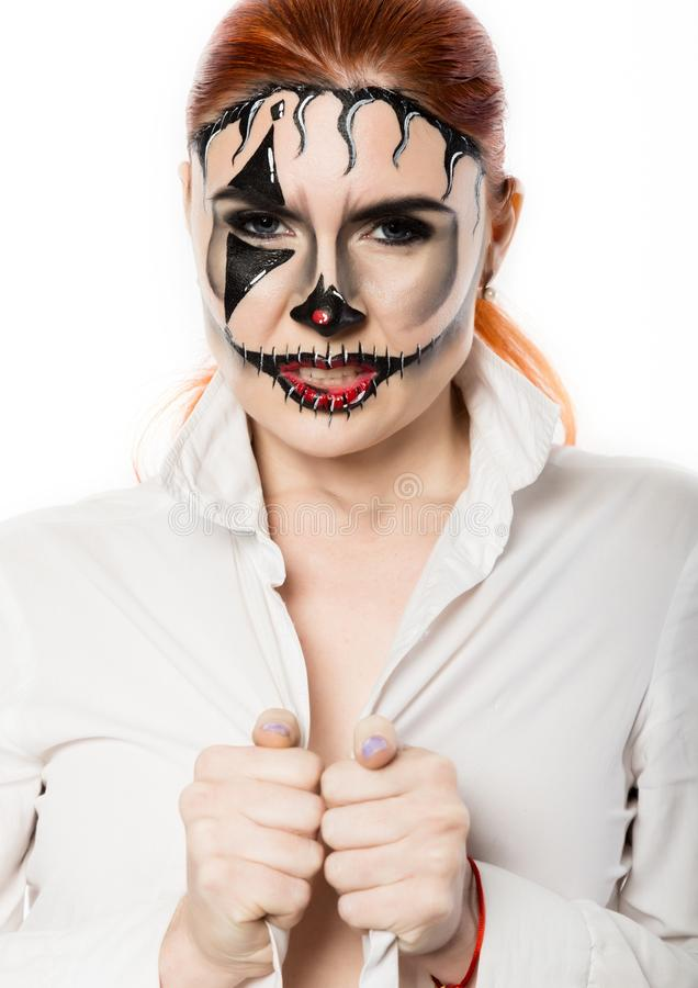 Beautiful girl with terrible mask painted on her face. Halloween and creative make-up. royalty free stock photography