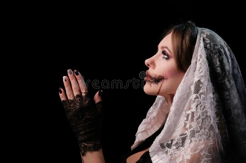 A beautiful girl in a terrible nun`s costume folded her arms as if she were reading a prayer. Woman with makeup for the Halloween stock photography