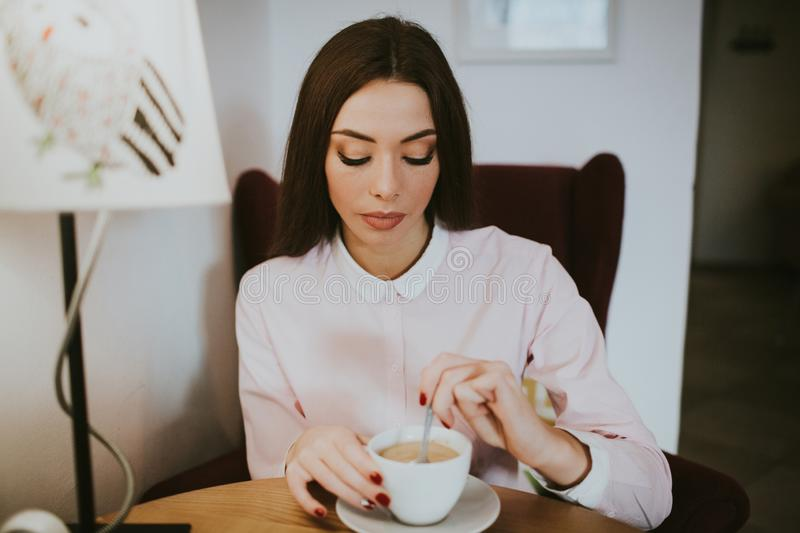 Beautiful girl thoughtfully drinks coffee in the cafe royalty free stock photos