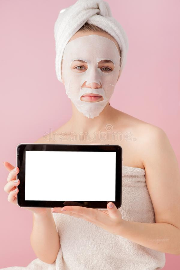 Beautiful girl with a tissue mask and a tablet in their hands with copy space on a pink background. Healthcare and beauty. Treatment and technology concept royalty free stock photos