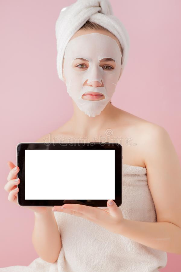 Beautiful girl with a tissue mask and a tablet in their hands with copy space on a pink background. Healthcare and beauty. Treatment and technology concept stock photo