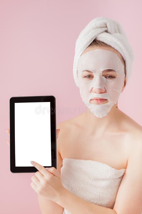 Beautiful girl with a tissue mask and a tablet in their hands with copy space on a pink background. Healthcare and beauty. Treatment and technology concept stock images