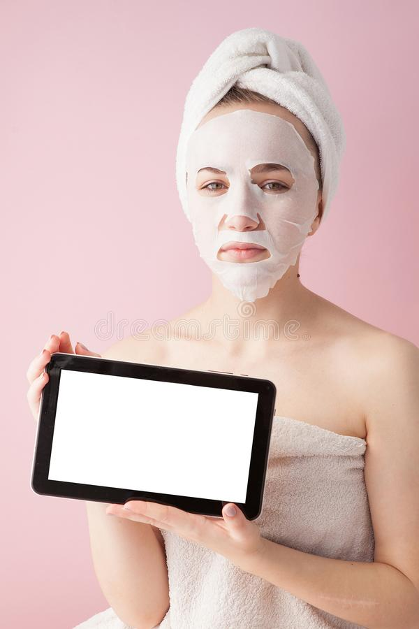 Beautiful girl with a tissue mask and a tablet in their hands with copy space on a pink background. Healthcare and beauty. Treatment and technology concept royalty free stock photo