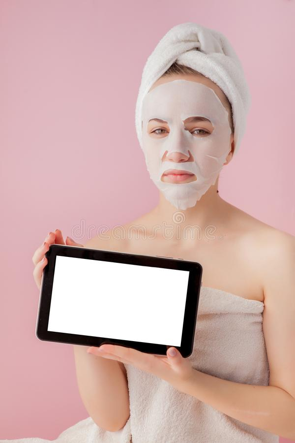 Beautiful girl with a tissue mask and a tablet in their hands with copy space on a pink background. Healthcare and beauty. Treatment and technology concept royalty free stock images
