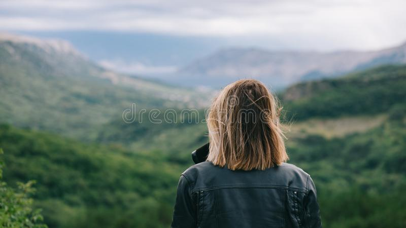 Beautiful girl on top of mountain watching scenery stock photography