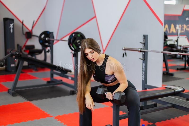Beautiful girl trains biceps with dumbbell sitting on the bench in the gym. stock photo
