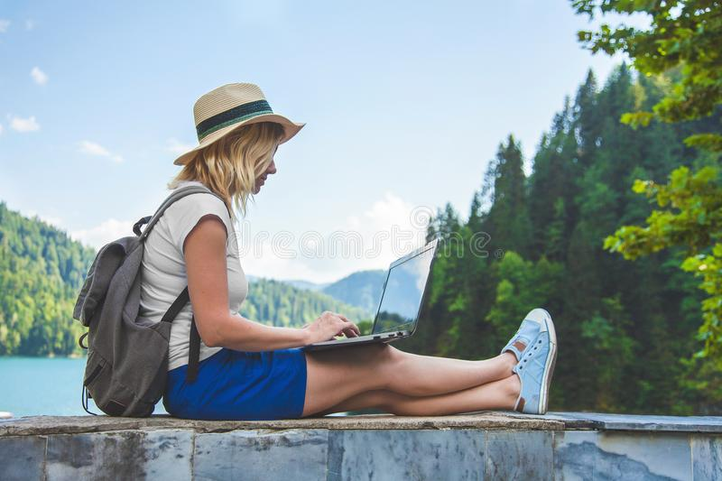 Beautiful girl traveler in a hat on a lake with a laptop stock photography