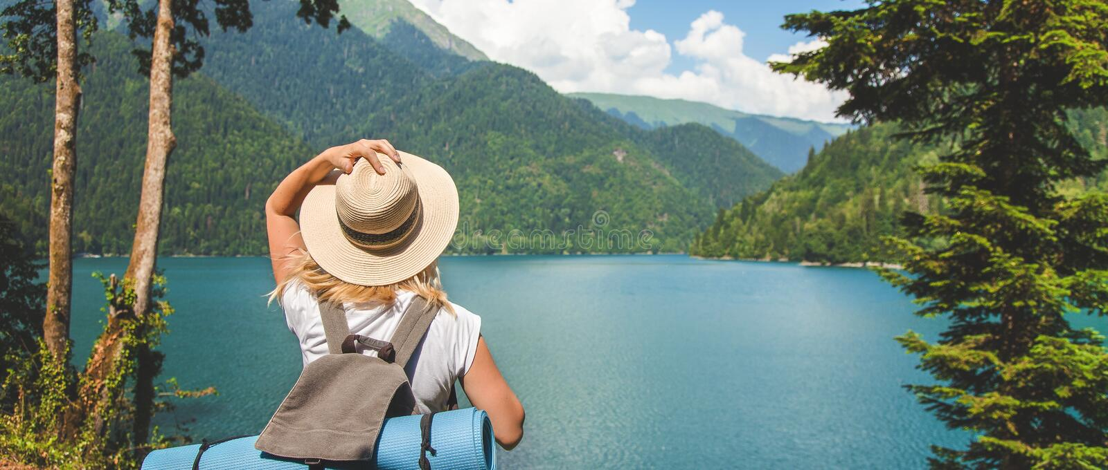 Beautiful girl traveler in a hat stands on a lake in the background of the mountains She enjoys the beauty of nature royalty free stock photos