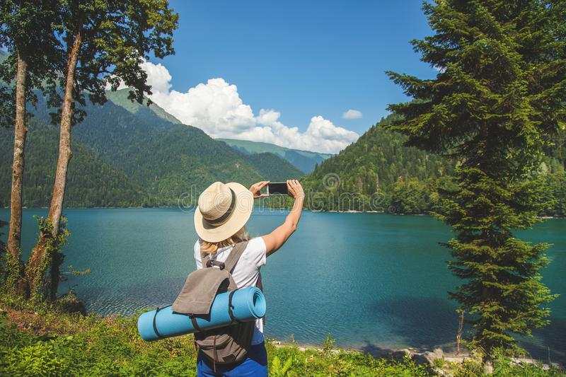 Beautiful girl traveler in a hat stands on a lake and takes pictures on a background of mountains Travel concept Summer vacation C royalty free stock photo