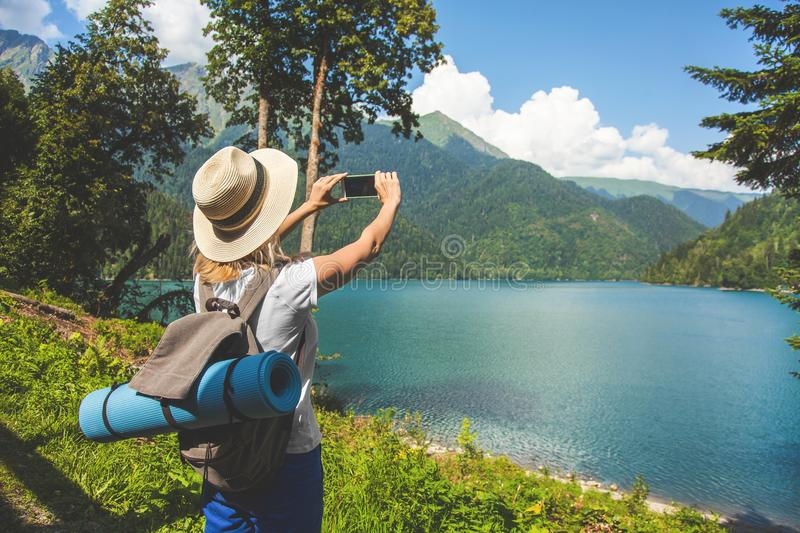 Beautiful girl traveler in a hat stands on a lake and takes pictures on a background of mountains royalty free stock photos