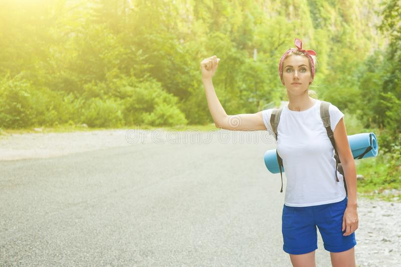 Beautiful girl traveler hitchhiking in the mountains. Toned Copy space royalty free stock photography