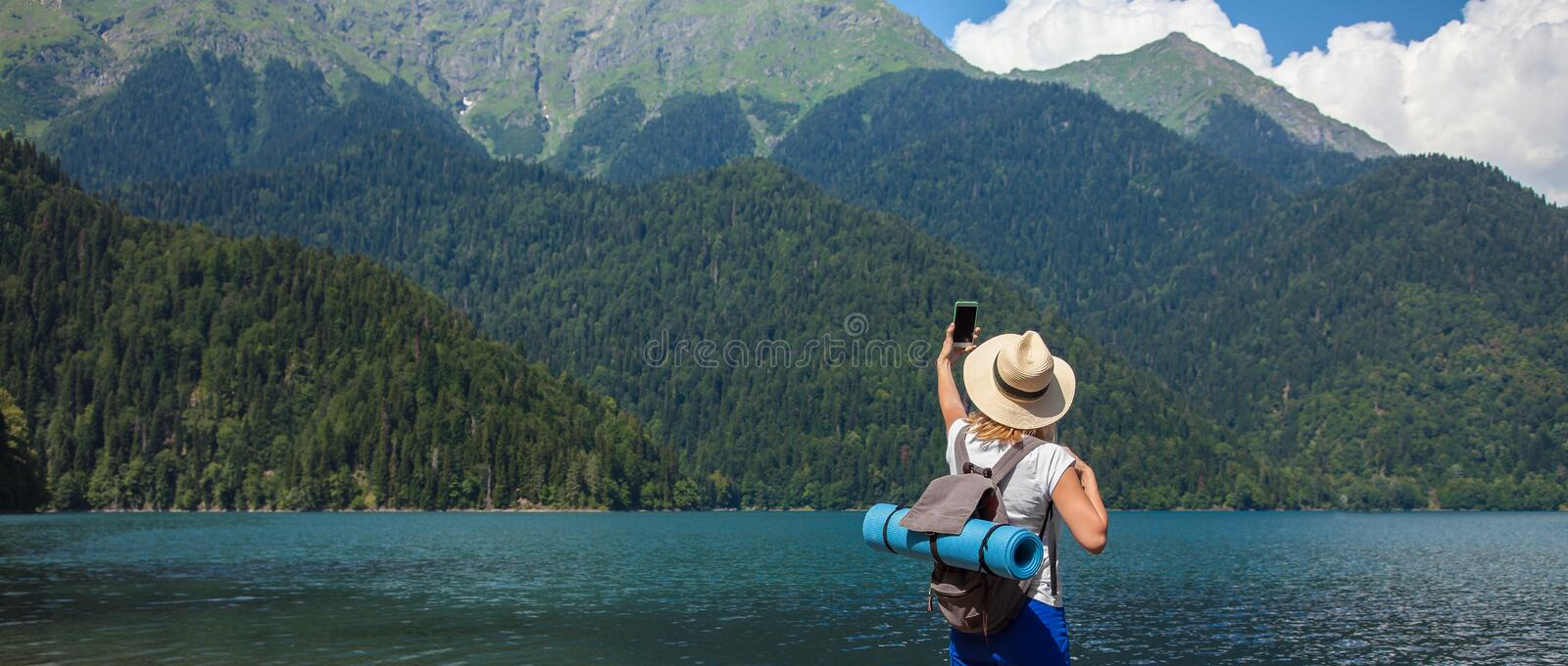 Beautiful Girl Traveler makes selfie on a large blue mountain lake in the background of the mountains royalty free stock photos
