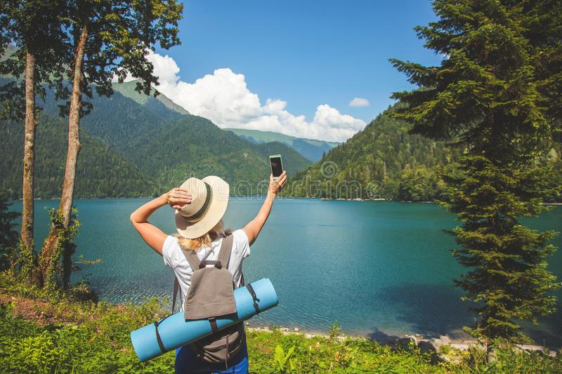 Beautiful Girl Traveler makes selfie on a large blue mountain lake in the background of the mountains royalty free stock photography