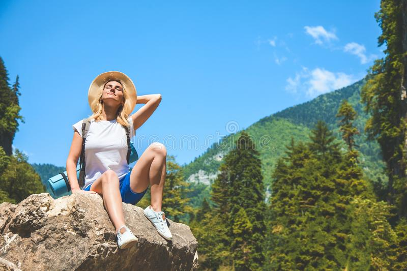 Beautiful Girl Traveler sits on a mountain and enjoys the sun on a background of mountains royalty free stock photography