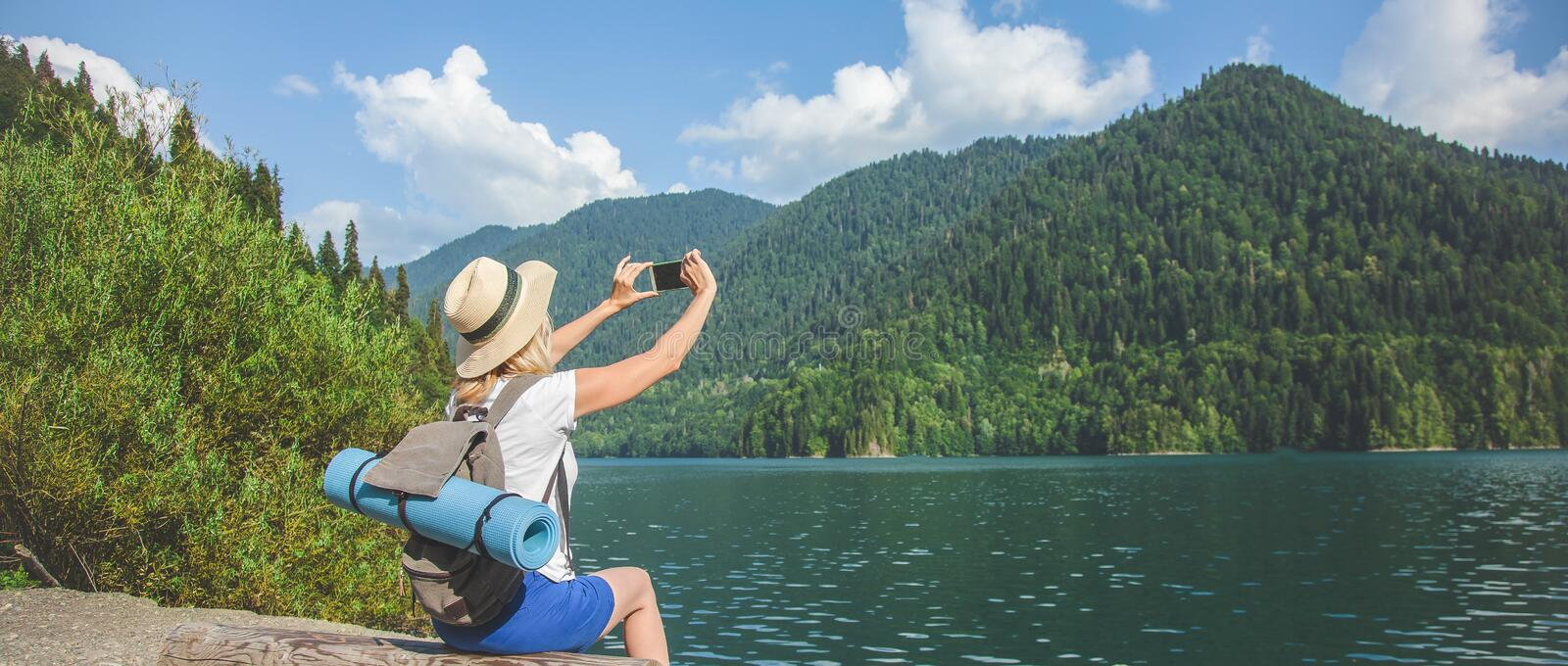 Beautiful Girl Traveler takes pictures of a large blue mountain lake in the background of the mountains stock image