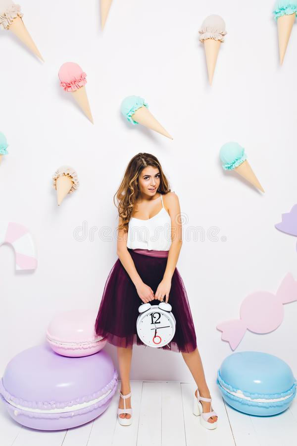 Beautiful girl in trendy violet skirt standing near the big toy macaroons and holding alarm clock. Portrait of elegant stock image
