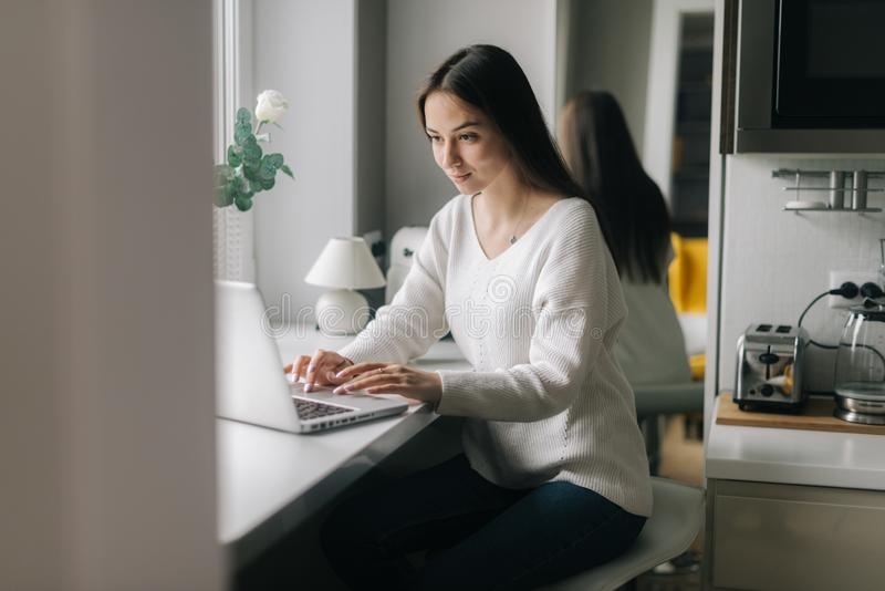Beautiful girl typing on her laptop sitting next to a window in the kitchen. royalty free stock photography